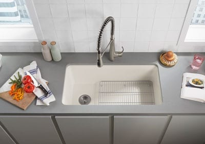 Birds-eye view of a white sink with garbage disposal and whole-home water filtration systems