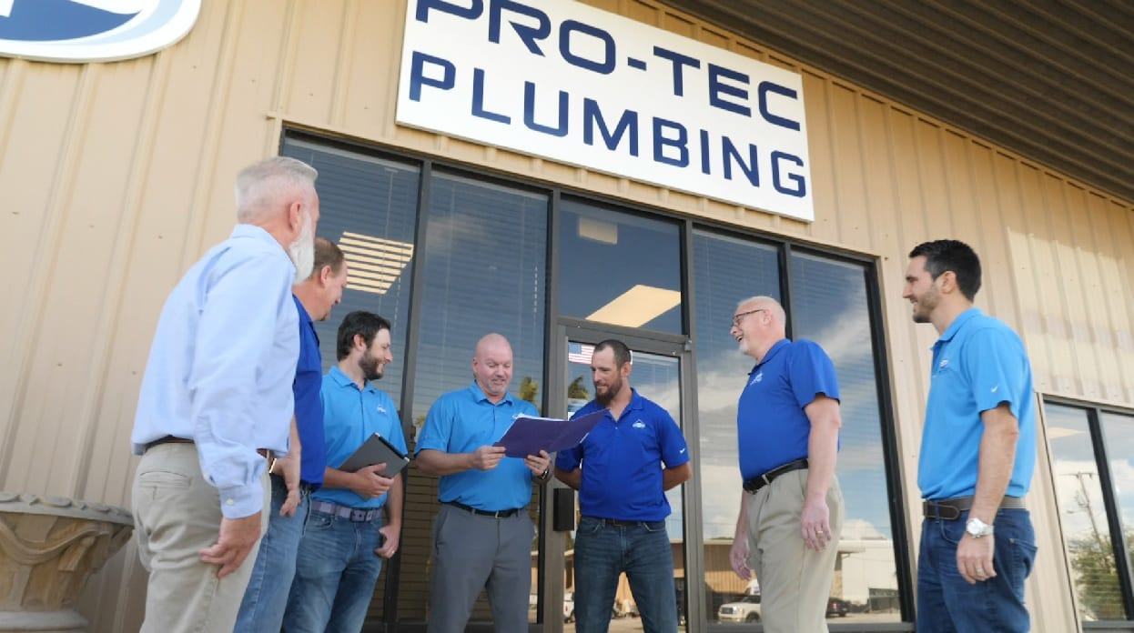 Our team header image featuring the Pro-Tec Plumbing & Drains Team standing in front of office building with paperwork